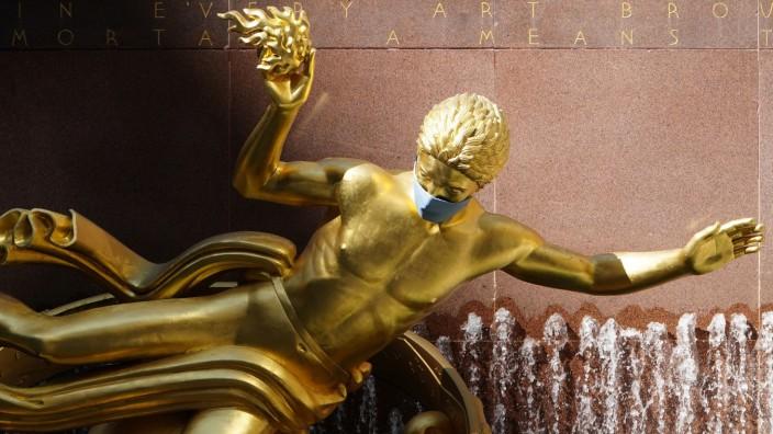 The statue of Greek Titan Prometheus wears a mask in Rockefeller Center during the coronavirus disease (COVID-19) pandemic