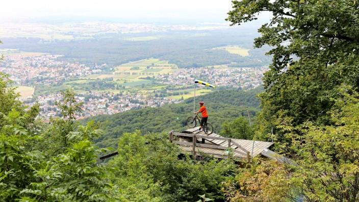 Mountainbiker steht auf der Startrampe für Drachenflieger unterhalb des Melibokus und blickt auf die Rheinebene (Model r
