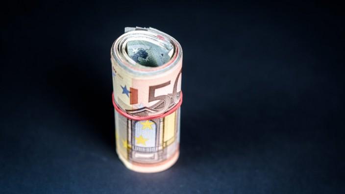Illustration Eine Geldrolle liegt auf einem Tisch