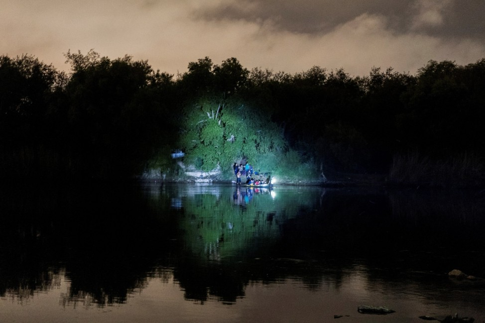 Asylum-seeking migrants cross the Rio Grande river in Roma, TX