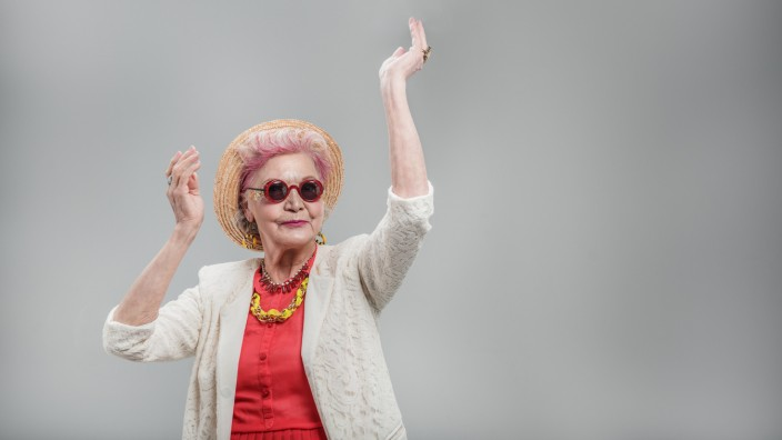 I want to move. Happy stylish senior lady in hat dancing with hands raised and smiling isolated on gray background (YakobchukOlena)