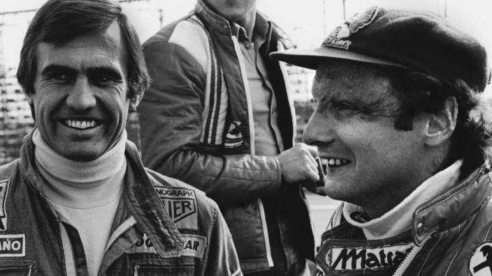 Jarama, Madrid, Spain. 6th - 8th May 1977. Carlos Reutemann and team mate Niki Lauda share a joke in the paddock, portr