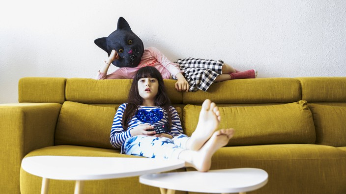 Creative Highlights Symbol Two bored girls sitting on couch, watching TV, one wearing cat mask model released Symbolfot