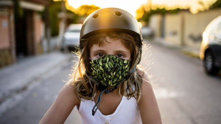 Girl wearing protective face mask and helmet during sunset model released Symbolfoto AMPF00020