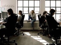 Coworkers working while female talking on phone in office Sweden, Stockholm, model released, property released Copyright