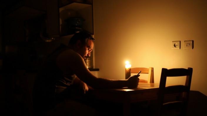 Ein iranischer Student liest in Irans Hauptstadt Teheran bei Kerzenlicht, um Strom zu sparen.