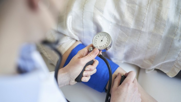 Close-up of doctor taking blood pressure of patient in medical practice model released Symbolfoto PUBLICATIONxINxGERxSU
