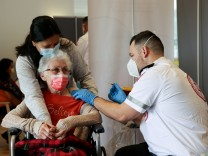 FILE PHOTO: A elderly woman receives a booster shot of her vaccination against the coronavirus disease (COVID-19) at an assisted living facility, in Netanya