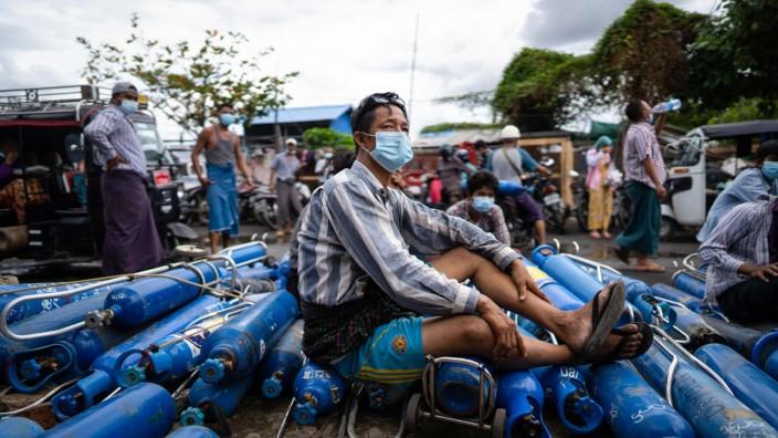 Myanmar: In der Stadt Mandalay wartet ein Mann vor einer Fabrik darauf, dass seine Sauerstoffflaschen gefüllt werden.