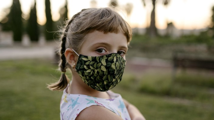 Girl with bangs and protective face mask staring while standing at park model released Symbolfoto AMPF00109