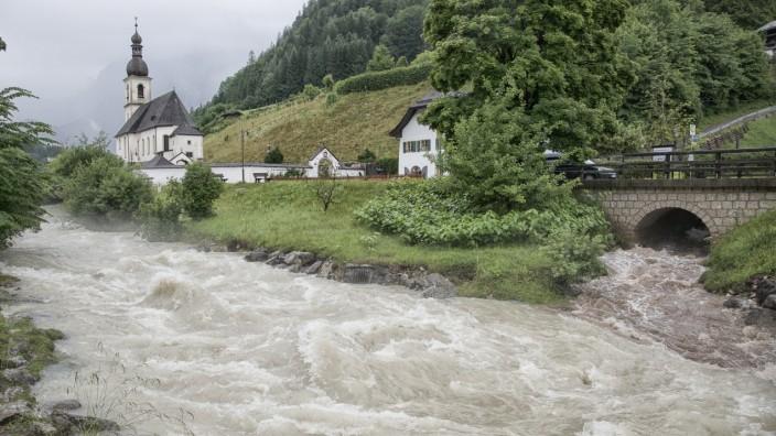 Katastrophenfall im Berchtesgadener Land: Der berühmte Postkartenblick auf die Kirche Sankt Sebastian in der Ramsau, neben der die Ache sonst gemächlich dahin fließt, hat im Moment nichts Romantisches mehr.