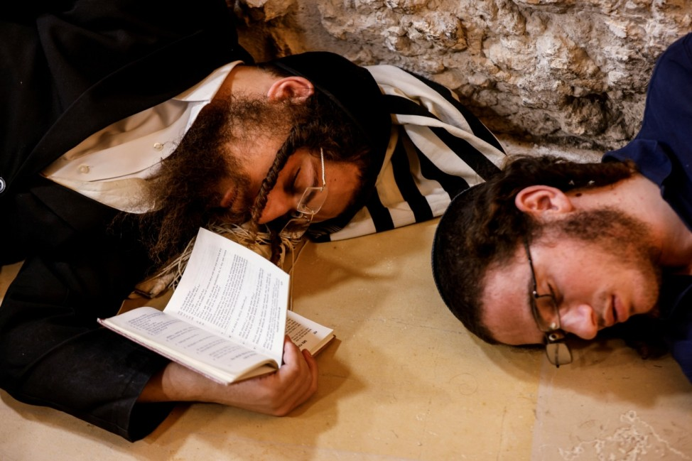 Jewish worshippers pray on Tisha B'Av, a day of fasting and lament, at the Western Wall in Jerusalem's Old City