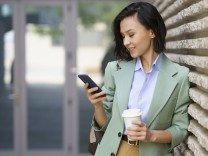 Businesswoman using smart phone while leaning on wall model released Symbolfoto JSMF02299