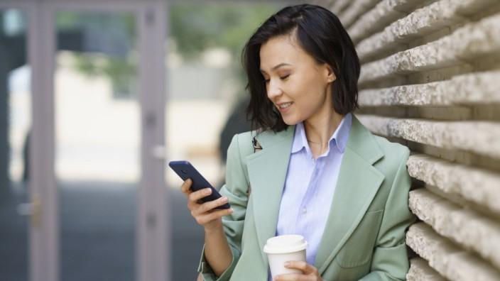 Handy: Eine junge Frau surft mit ihrem Smartphone