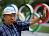 Kohei Jinno speaks in front of the Olympic Rings monument near the Natioonal Stadium in Tokyo