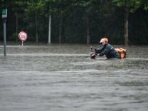 (210720) -- ZHENGZHOU, July 20, 2021 -- A courier wades through a waterlogged road in Zhengzhou, capital of central Chi