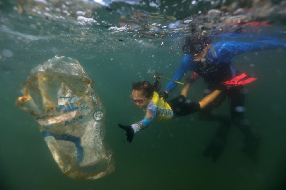 Nina Gomes, who was named as the youngest 'Green Agent' by the Municipal Urban Cleaning Company, collects garbage in the sea in Rio de Janeiro