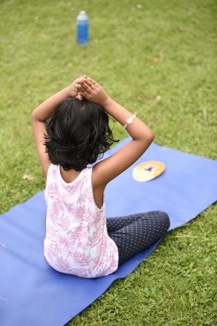 Lerchenau: Die jungen Yoga-Schülerinnen strecken die Arme in die Höhe oder sitzen im Schneidersitz auf ihren Yoga-Matten.