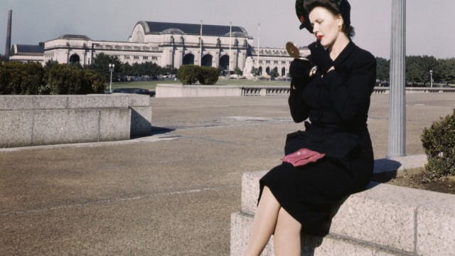 Woman putting on Lipstick in Park with Union Station in Background, Washington, D.C., USA, U.S. Office of War Informatio