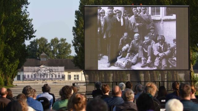 """KZ-Gedenkstätte Dachau: 200 Besucher schauen auf einer Leinwand, die im hinteren Teil der Lagerstraße aufgebaut ist, zum ersten Mal den neuen Besucherfilm """"Das Konzentrationslager Dachau"""". Fast drei Jahre haben die drei Filmschaffenden Maya Schweizer, Benjamin Meyer-Krahmer und Clemens von Wedenmeyer daran gearbeitet."""