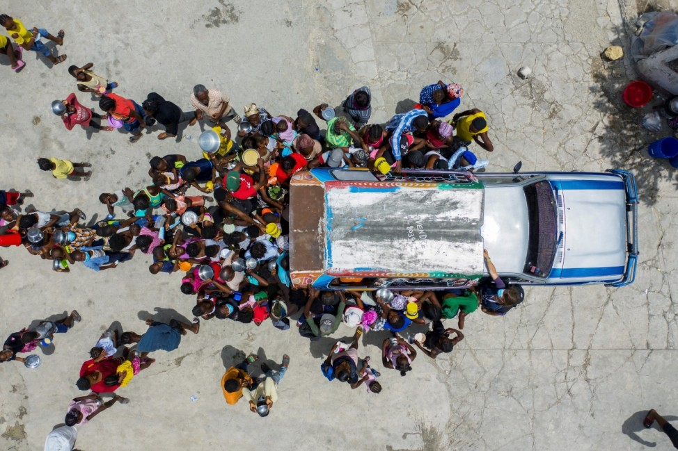 People gather around a car where volunteers distribute food to refugees at a shelter for families displaced by gang violence at the Saint Yves Church in Port-au-Prince