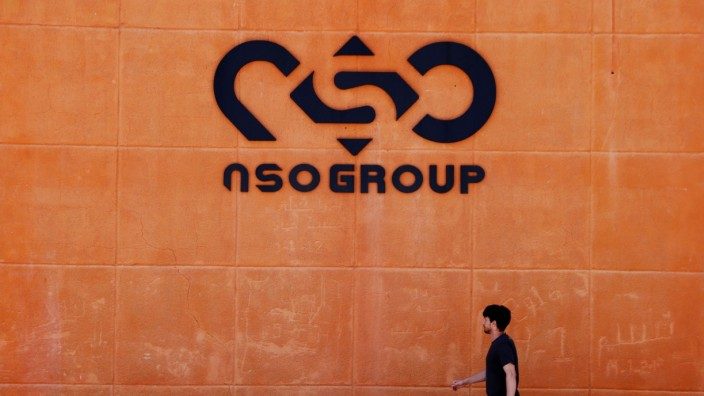 A man walks past the logo of Israeli cyber firm NSO Group at one of its branches in the Arava Desert, southern Israel