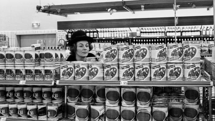 Eine Kundin sucht in den Regalgängen der Konservenabteilung in einem Supermarkt in Hamburg Deutschl