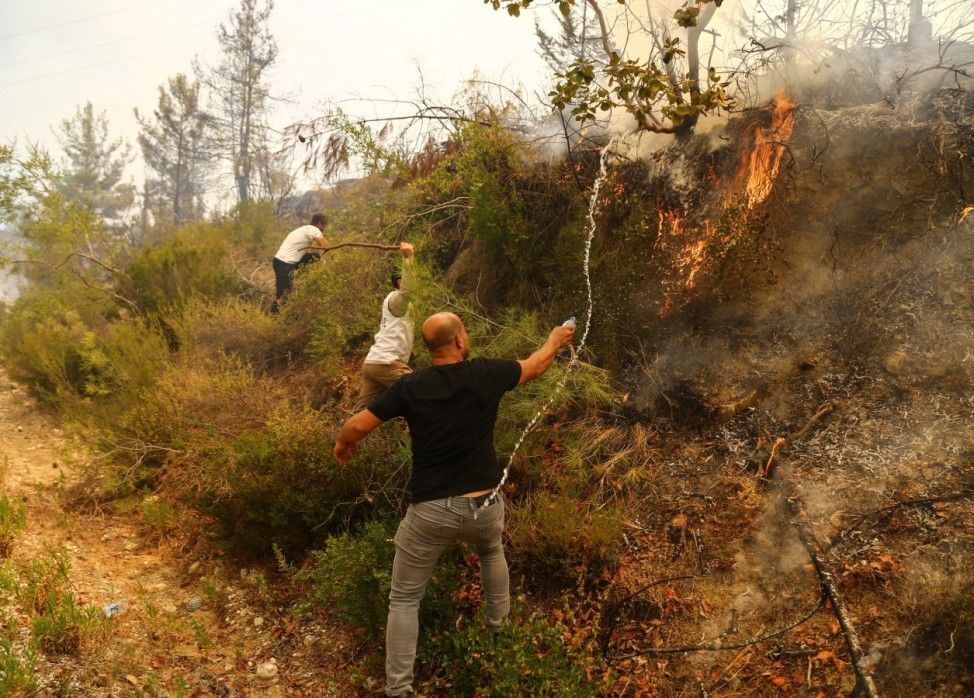 Locals try to extinguish a wildfire near the town of Manavgat