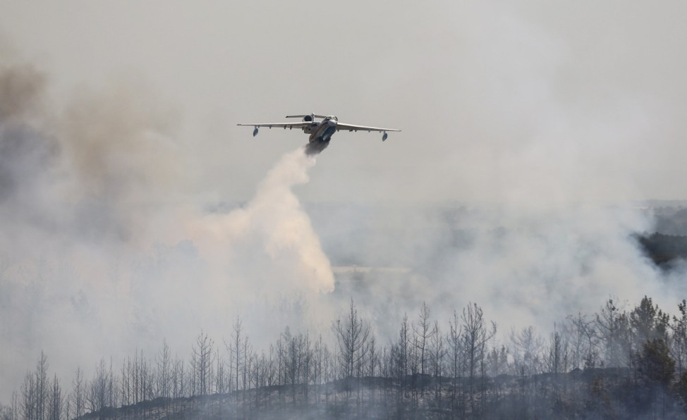 A firefighting aircraft drops water on a wildfire near the town of Manavgat