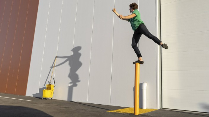 Acrobat standing on pole casting shadow at cleaning bucket model released Symbolfoto PUBLICATIONxIN