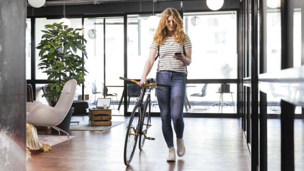 Businesswoman using mobile phone while walking with bicycle in office model released Symbolfoto property released FKF042