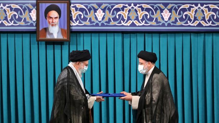 Iran: Der Oberste Führer, Ayatollah Ali Chamenei (links), führt den neuen Präsidenten Ebrahim Raisi ins Amt ein, und das Chomeini-Foto ist natürlich dabei: Teheran am gestrigen Dienstag.