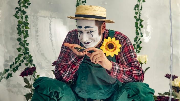 Straßentheater: Bastian, die Figur des Clowns Sebastian Weiß, zeigt den Tollwood-Besuchern seine kleine Gartenwelt.