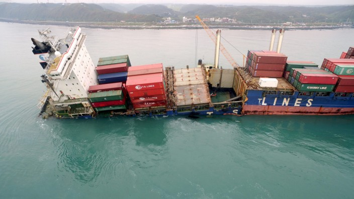 Taiwan tries to contain oil spill from grounded container