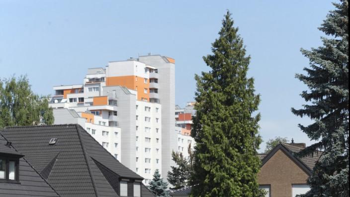 Wohnen: Einfamilienhäuser vor Plattenbauten in Bremen: Geringverdiener müssen mit deutlich weniger Platz auskommen und wohnen seltener in neu gebauten Objekten als Besserverdiener.