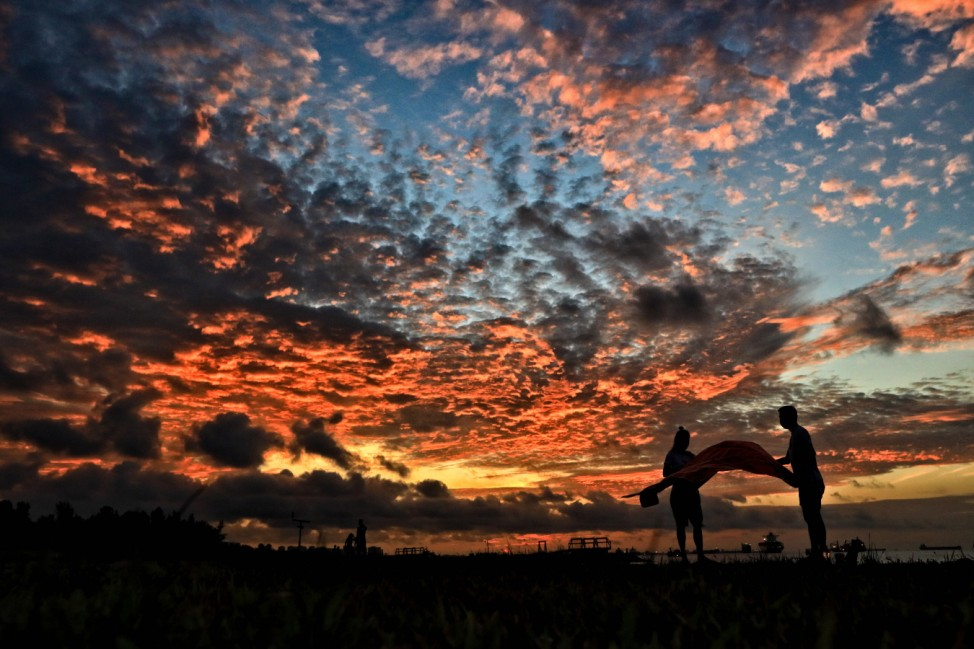 Daily Life Amid Singapore Heightened Alert For COVID-19 A couple prepares to lay a picnic mat to watch the sunrise on A