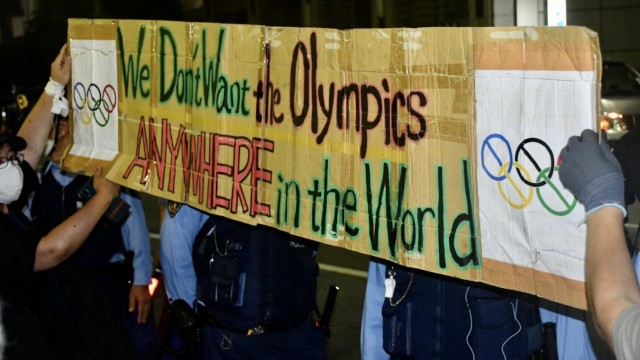 TOKYO, JAPAN - AUGUST 8, 2021: Demonstrators hold a banner with a message reading We Don t Want the Olympics Anywhere i