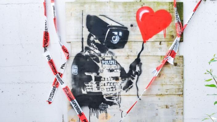 Oberschleißheim: Mit Liebe gegen den Überwachungsstaat: das Wandbild eines anonymen Graffiti-Künstlers in Oberschleißheim.