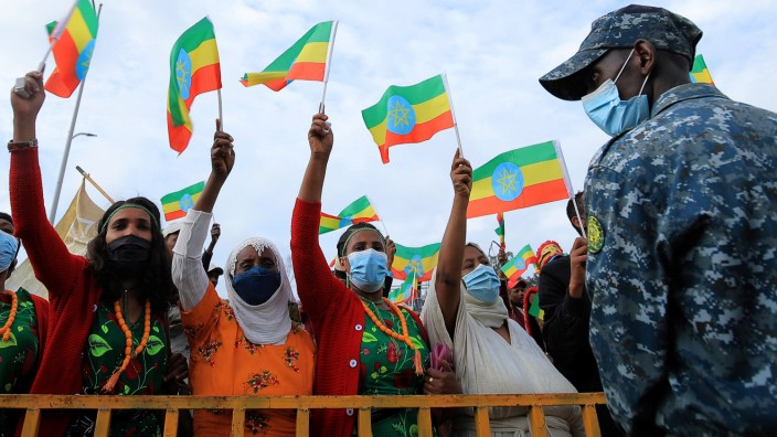 Women hold national flag during a rally to support the National Defense Force at the Meskel Square in Addis Ababa