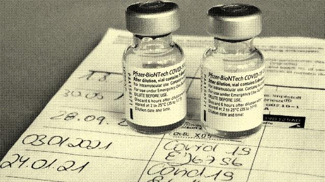Symbolbild Corona-Impfung. Zwei Impfdosen und der Eintrag der ersten und zweiten Corona-Impfung in einem Impfpass einer