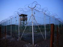 FILE PHOTO: Chain link fence and concertina wire surrounds a deserted guard tower within Joint Task Force Guantanamo's Camp Delta