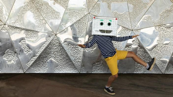 Boy wearing robot mask dancing on footpath against patterned wall model released Symbolfoto VABF03128