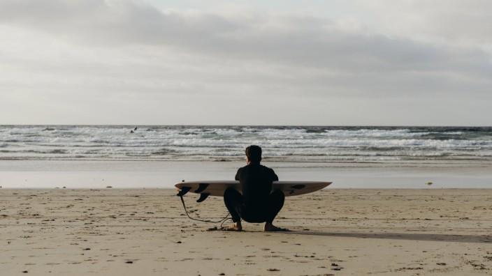 Back view of unrecognizable male surfer in wetsuit preparing surfboard on empty sandy coast of Lanzarote island in Spain