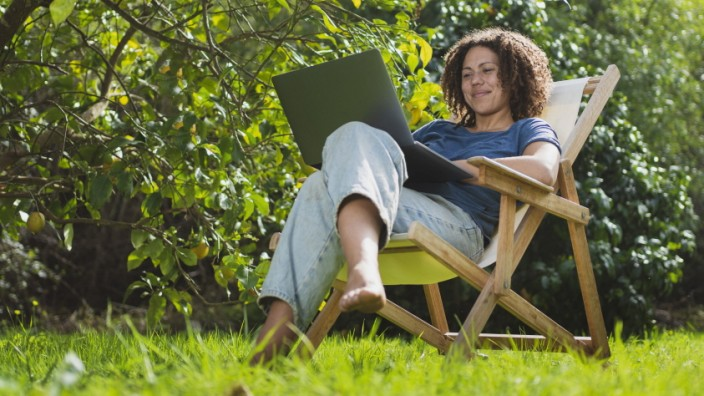 Smiling woman looking at laptop while sitting on chair in permaculture garden model released Symbolfoto property release