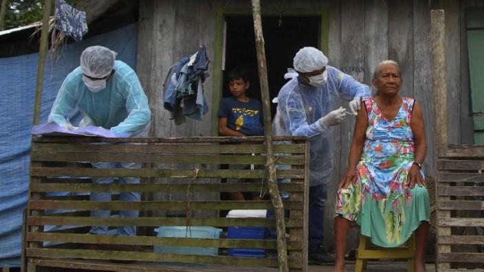 Brasilien und Corona: Bis weit in den Regenwald hinein machen sich die brasilianischen Impfteams auf. Die 72-jährige Maria Castro de Lima erhält ihre Spritze zur Abwehr des Coronavirus am Rio Purus.