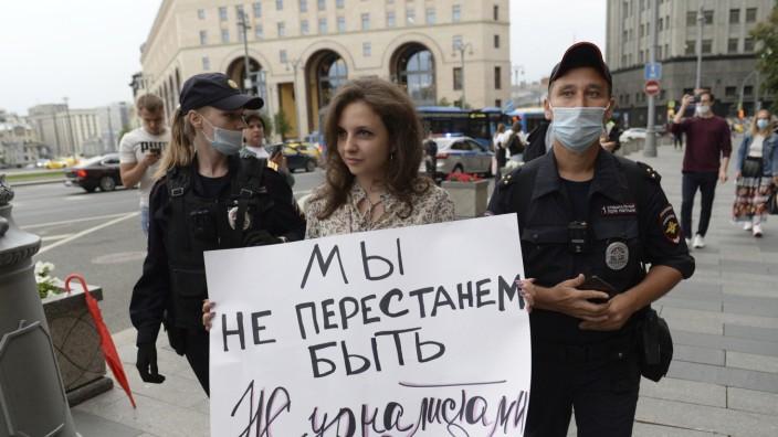"""Pressefreiheit in Russland: Ende einer Mahnwache in Moskau: Polizisten nehmen eine Journalistin fest, auf deren Schild geschrieben steht: """"Wir werden nicht aufhören Journalisten zu sein"""""""