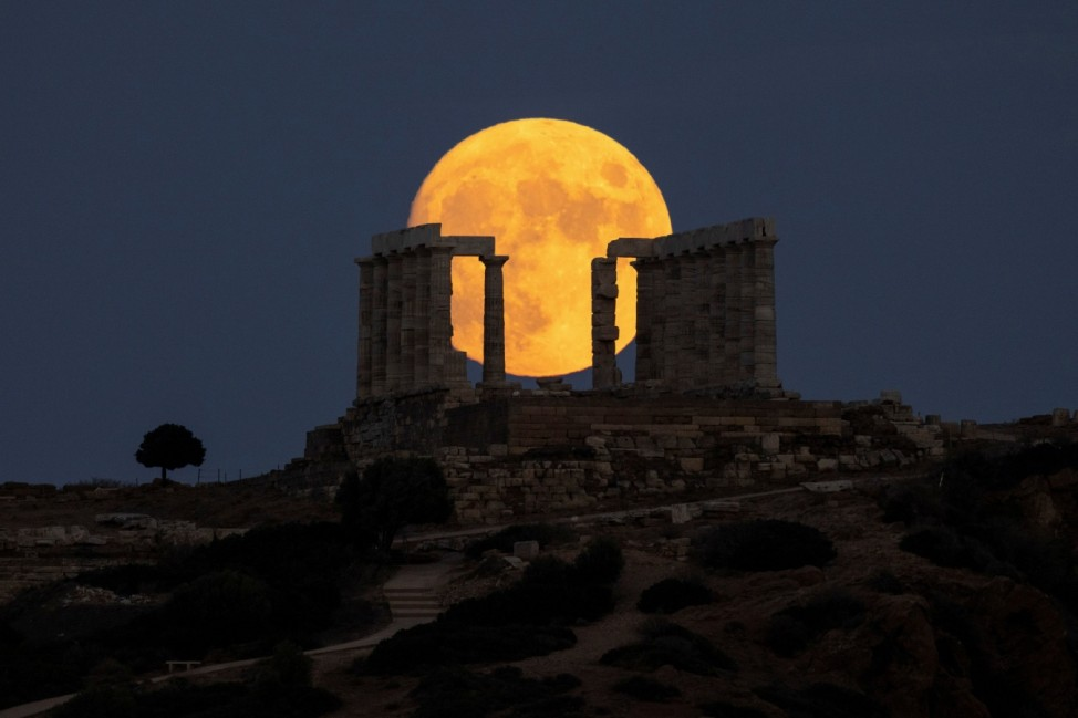 An almost full moon rises over the Temple of Poseidon in Cape Sounion, near Athens
