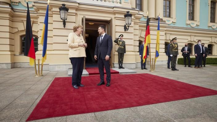 """Ukraine: """"Danke, Angie"""": Der ukrainische Präsident Wolodimir Selenskij begrüßt Bundeskanzlerin Angela Merkel vor seinem Amtssitz in Kiew."""