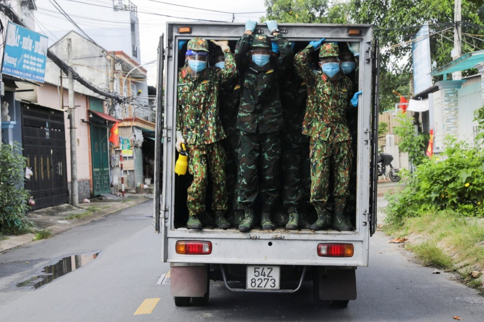 Vietnam soldiers are seen in a truck as they deliver food in strict lockdown areas amid the coronavirus disease (COVID-19) pandemic in Ho Chi Minh