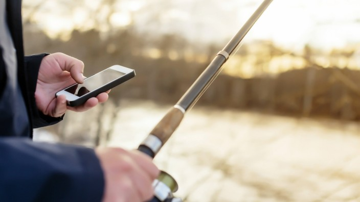 Man fishing looking at cell phone model released Symbolfoto PUBLICATIONxINxGERxSUIxAUTxHUNxONLY KNTF